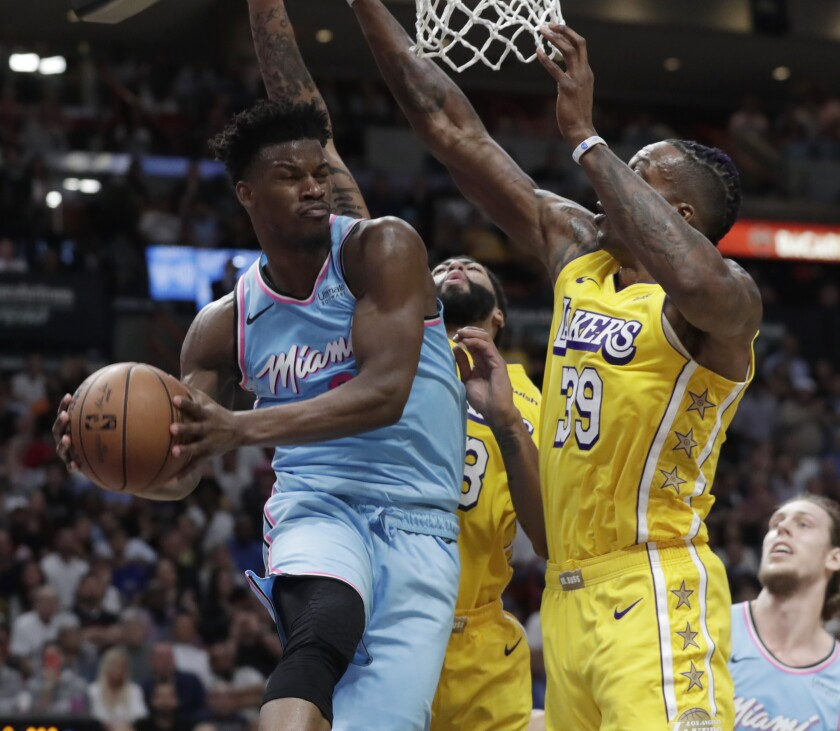 The Heat's Jimmy Butler looks to pass against Lakers defenders Dwight Howard (39) and Anthony Davis during a game Dec. 13.