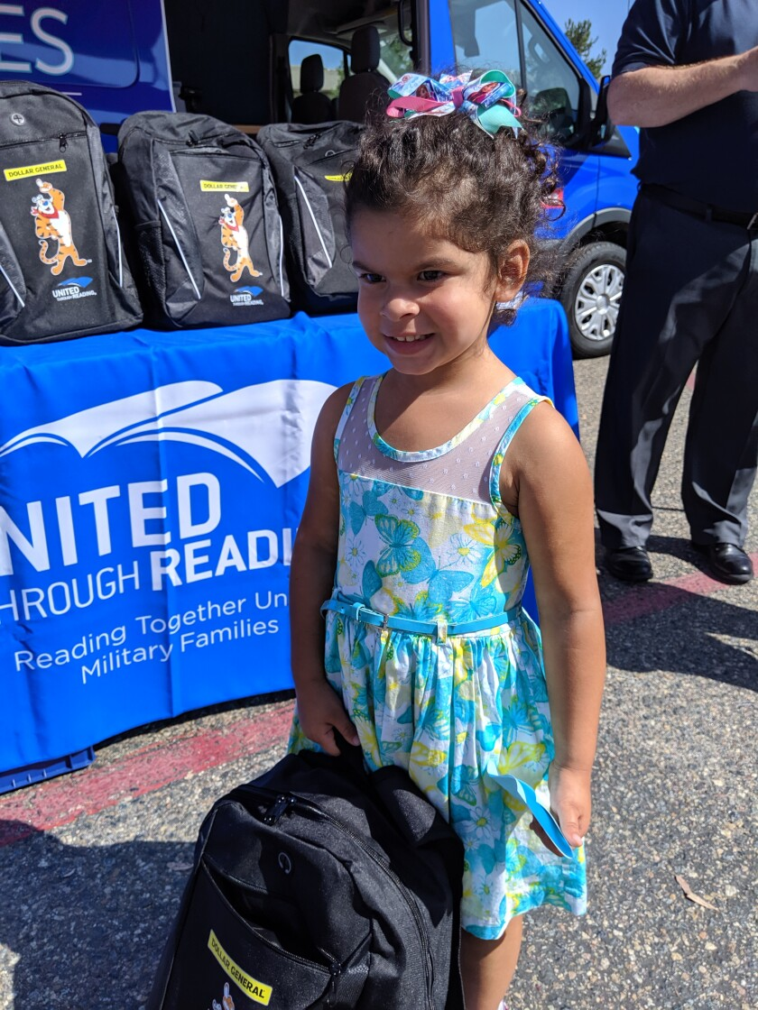 A student shows off her backpack at the donation event sponsored by Dollar General stores and United Through Reading.