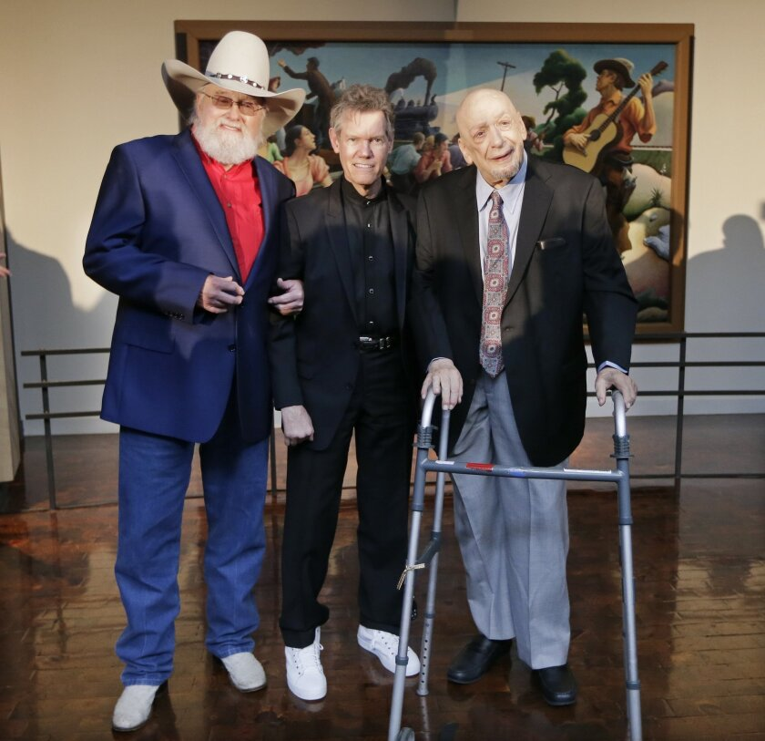 Fiddler Charlie Daniels, left, singer Randy Travis, center, and producer and label owner Fred Foster pose Tuesday, March 29, 2016, in Nashville, Tenn., after it was announced they will be inducted into the Country Music Hall of Fame. (AP Photo/Mark Humphrey)