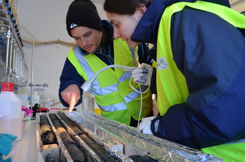 Geochemist Juerg Matter and microbiologist Rosalia Trias inspect basalt core for solidified carbon dioxide.