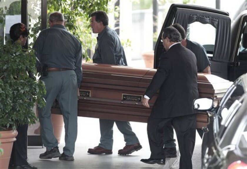 Cemetery workers carry the casket with  the body of former Venezuelan President Carlos Andres Perez to be temporarily entombed in a crypt  in Miami, Thursday, June 30, 2011. Perez died Dec. 25 at age 88. His estranged wife says she has the right to bury him in Venezuela. But his longtime companion