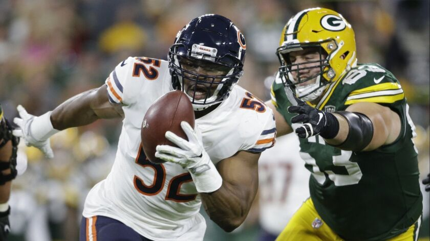 In this Sunday, Sept. 9, 2018, file photo, Chicago Bears' Khalil Mack (52) intercepts a pass and returns it for a touchdown as Green Bay Packers' Corey Linsley (63) gives chase during the first half in Green Bay, Wis.
