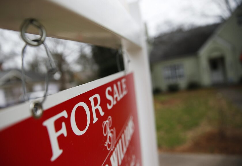 """FILE - This Jan. 26, 2016 file photo shows a """"For Sale"""" sign hanging in front of an existing home in Atlanta. Short of savings and burdened by debt, America's millennials are struggling to afford their first homes in the face of sharply higher prices in many of the most desirable cities. Surveys show that most Americans under 35 lack adequate savings for down payments. The result is that many will likely be forced to delay home ownership and to absorb significant debt loads if they do eventually buy. (AP Photo/John Bazemore, File)"""