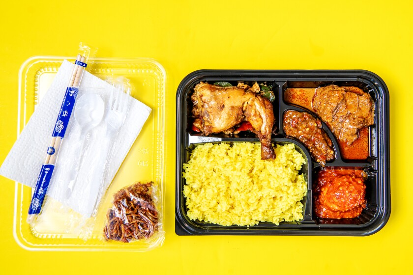 A plastic to-go tray filled with chicken and side dishes, with chopsticks