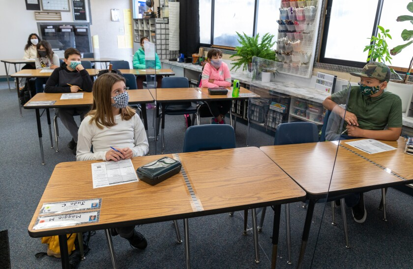 McAuliffe Elementary fifth graders are separated by plexiglass between tables in Oceanside Unified.