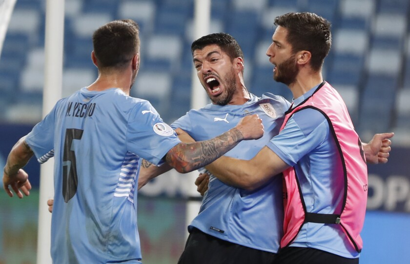 Uruguay's Luis Suarez, center, celebrates scoring his team's opening goal against Chile during a Copa America soccer match at Arena Pantanal stadium in Cuiaba, Brazil, Monday, June 21, 2021. (AP Photo/Andre Penner)