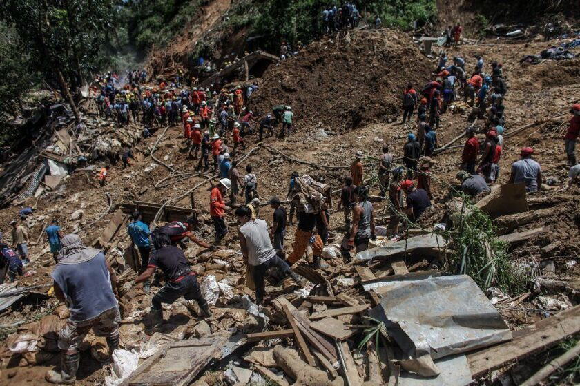 Filipino rescuers dig Tuesday at the site where dozens of people were believed to have been buried by a landslide triggered by Typhoon Mangkhut.