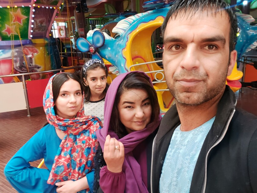 A woman in a dark pink head covering is flanked by two girls on the left and a man