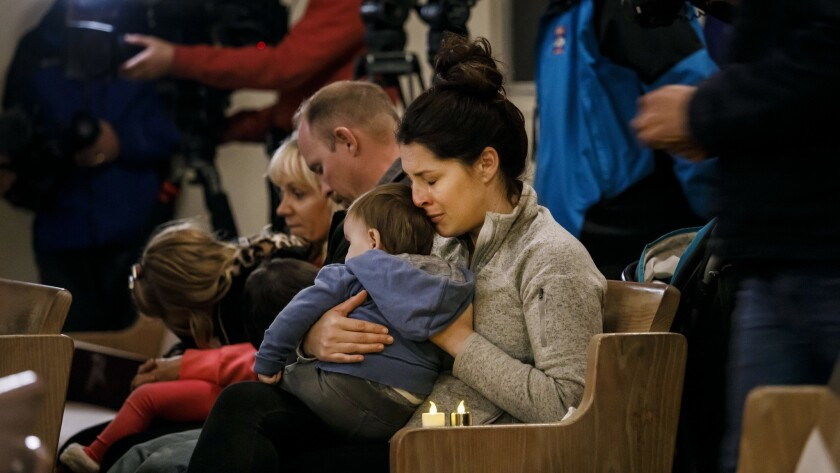 Kristy Collins embraces her 9-month-old son Andrew during a vigil for the those who died in the Camp fire — and prayers for the first responders — at First Christian Church in Chico, Calif., on Nov. 18.