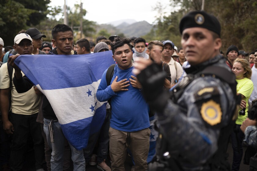FILE - In this Jan. 16, 2020 file photo, Honduran migrants hoping to reach the U.S. border are stopped by Guatemalan police near Agua Caliente, Guatemala, on the border with Honduras. The reasons Hondurans continue to flee their country have been well documented: pervasive violence, deep-seated corruption, lack of jobs and widespread destruction from two major hurricanes that struck the region last November. (AP Photo/Santiago Billy, File, File)