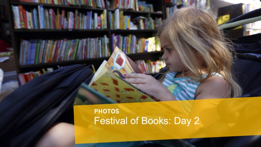Lillian Larkins, 4, sits in her stroller and checks out a book at the 20th Los Angeles Times Festival of Books at USC on Sunday.