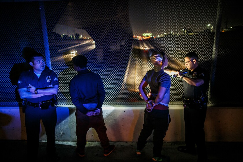 Officers from the LAPD's Metropolitan Division check a driver and passenger for tattoos while other officers search their vehicle in November 2015.