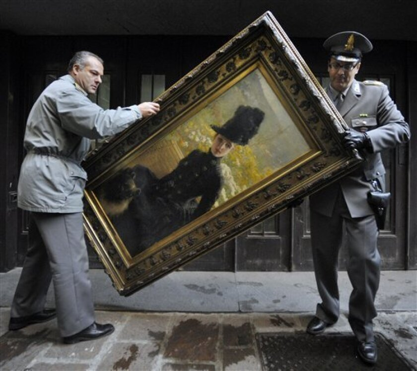 Italian tax police officers hold a Giuseppe De Nittis painting, one of the 19 masterpieces which was seized in Parma, Italy, Saturday, Dec. 5, 2009. Italian tax police have seized a secret attic and basement stash of Van Gogh, Picasso, Monet, Cezanne and other art works from the disgraced founder of Parmalat, the dairy company that collapsed a few years ago under billions of dollars of debt. Authorites estimated the total value of the works at more than euros 100 million. (AP Photo/Marco Vasini)