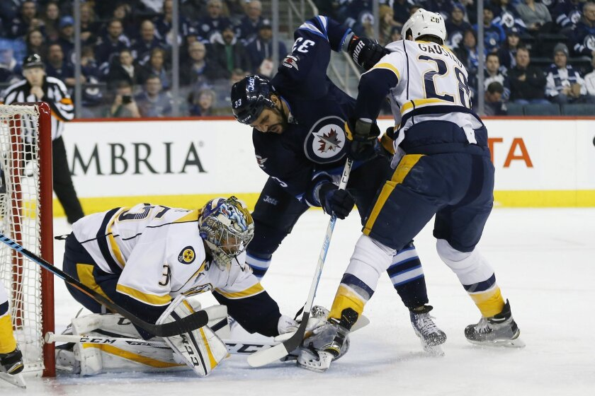Nashville Predators goaltender Pekka Rinne (35) jumps on the loose puck as Winnipeg Jets' Dustin Byfuglien (33) looks for the rebound and Predators' Paul Gaustad (28) defends during the second period of an NHL hockey game Thursday, Jan. 21, 2016, in Winnipeg, Manitoba. (John Woods/The Canadian Press via AP)