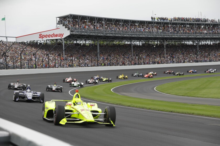 Cars take the first turn at the start of the 2019 Indianapolis 500. This year the fan crowd will be limited to half capacity.