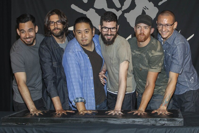 In this June 18, 2014 file photo, members of Linkin Park, from left, Mike Shinoda, Rob Bourdon, Joe Hahn, Brad Delson, Dave Farrell and Chester Bennington attend an induction ceremony for the Guitar Center's RockWalk at Guitar Center in Los Angeles. Linkin Park said their hearts are broken following the death of Bennington, who died by hanging last week. (Paul A. Hebert/Invision/AP, File)