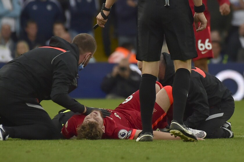 Liverpool's Harvey Elliott is assisted after he got injured in a clash with Leeds United's Pascal Struijk during the English Premier League soccer match between Leeds United and Liverpool at Elland Road, Leeds, England, Sunday, Sept. 12, 2021. (AP Photo/Rui Vieira)