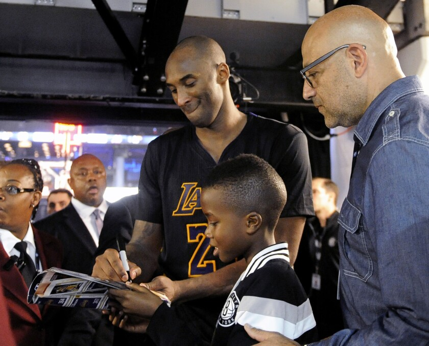 Lakers forward Kobe Bryant signs an autograph for a young fan as he walks off the court following a game against the Nets.