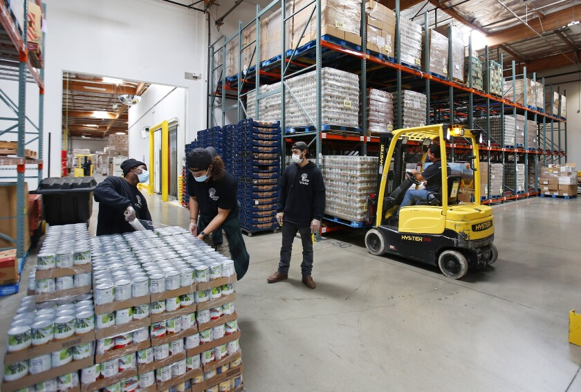 Workers sort food at the Jacobs & Cushman San Diego Food Bank on April 14, 2020.