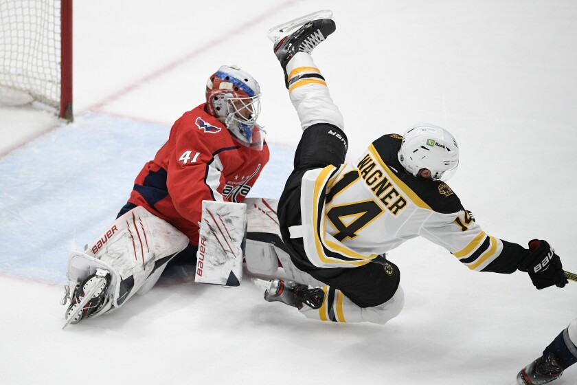 Boston Bruins right wing Chris Wagner (14) tumbles to the ice in front of Washington Capitals goaltender Vitek Vanecek (41) during the second period of an NHL hockey game, Tuesday, May 11, 2021, in Washington. (AP Photo/Nick Wass)