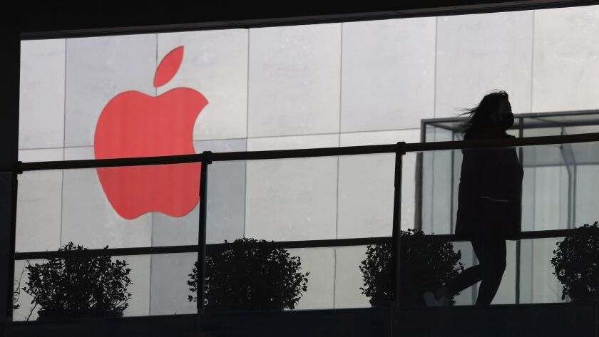 In this Dec. 6, 2018, photo, a woman runs past a Apple logo colored red in Beijing, China. Apple Inc