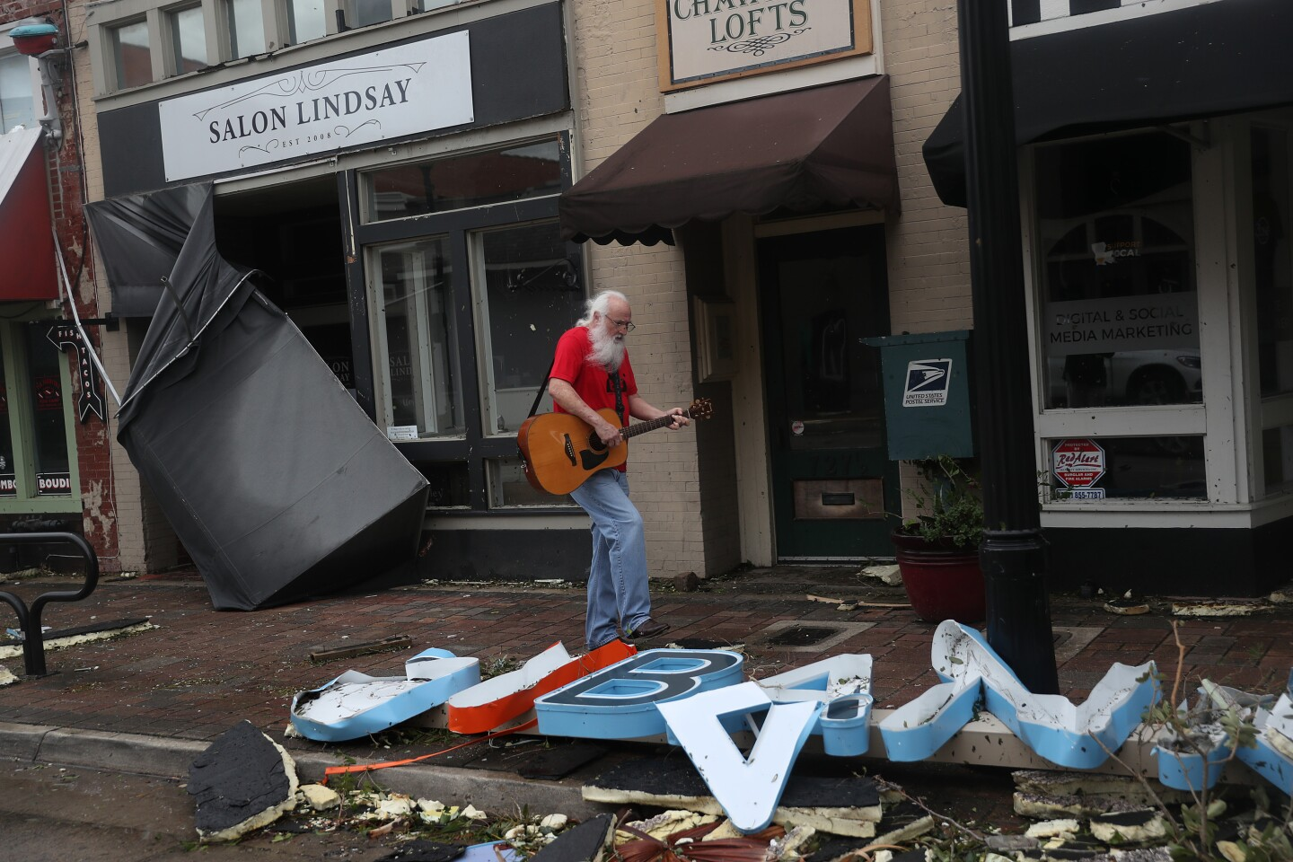 LAKE CHARLES, LOUISIANA - AUGUST 27: Mitch PIckering plays his guitar while walking through the downtown area after Hurricane Laura passed through on August 27, 2020 in Lake Charles, Louisiana . The hurricane hit with powerful winds causing extensive damage to the city. (Photo by Joe Raedle/Getty Images)