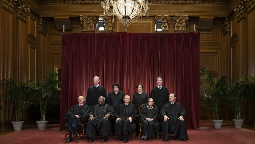 The Supreme Court justices gather for a formal group portrait at the Supreme Court Building in Washington on Nov. 30, 2018.