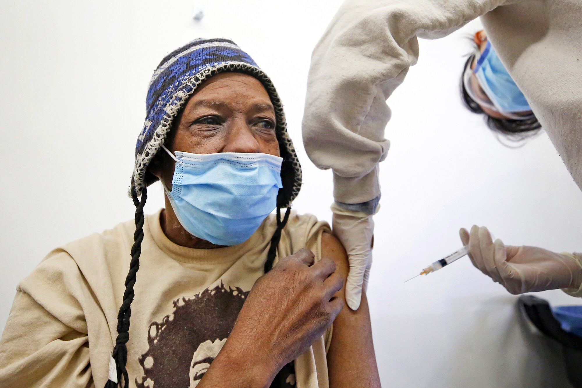 A man receives a vaccination from a nurse.