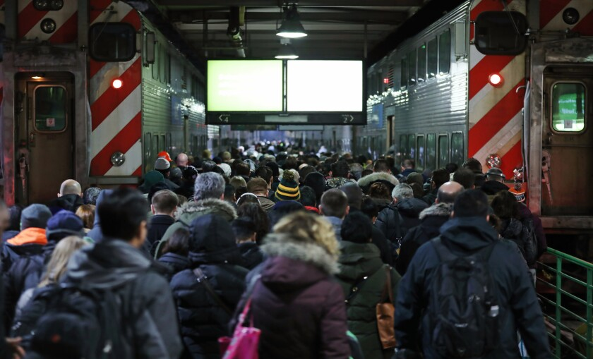 A crowd of Metra passengers head for a BNSF line train to depart from Union Station on Feb. 28, 2019, in Chicago. An Amtrak computer signal problem caused trains to be delayed throughout the day.
