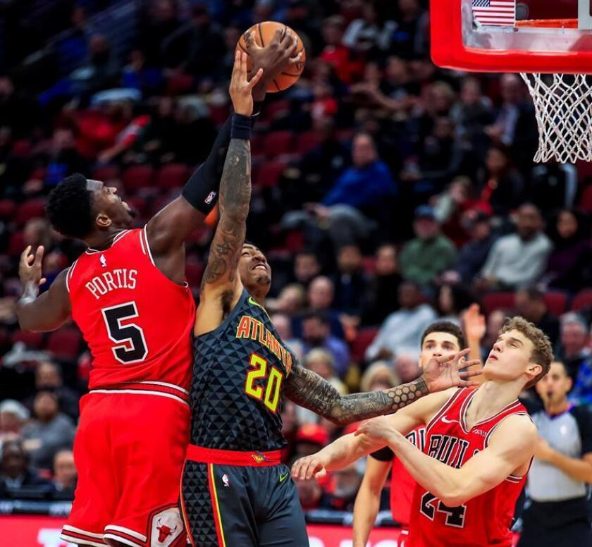 John Collins (c) de los Hawks en acción ante Bobby Portis (i) de los Bulls durante un partido de baloncesto de la NBA entre Atlanta Hawks y Chicago Bulls, este miércoles, en el United Center de Chicago, Illinois (EE.UU.). EFE