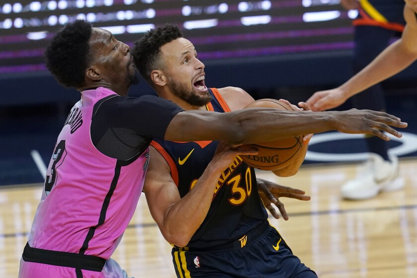 Golden State Warriors guard Stephen Curry, right, is fouled by Miami Heat center Bam Adebayo during the second half of an NBA basketball game in San Francisco, Wednesday, Feb. 17, 2021. (AP Photo/Jeff Chiu)