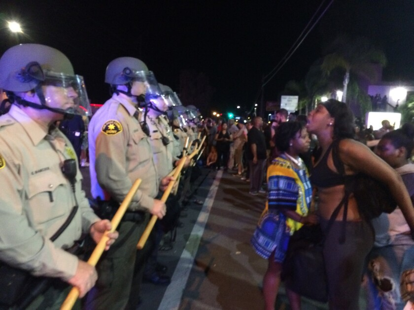 Demonstrators yell at police in El Cajon at a rally against the shooting of Alfred Olango.