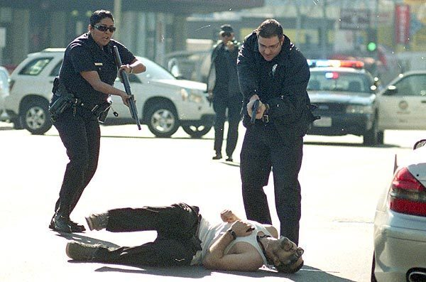LAPD officers run with guns drawn to the suspected gunman after the shooting spree on Vine Street in Hollywood.