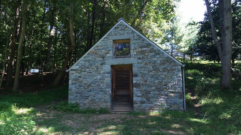 """A path along a creek leads to three stone houses crafted by British-born sculptor Andy Goldsworthy. Each of the so-called """"Clay Houses"""" features a work in clay."""