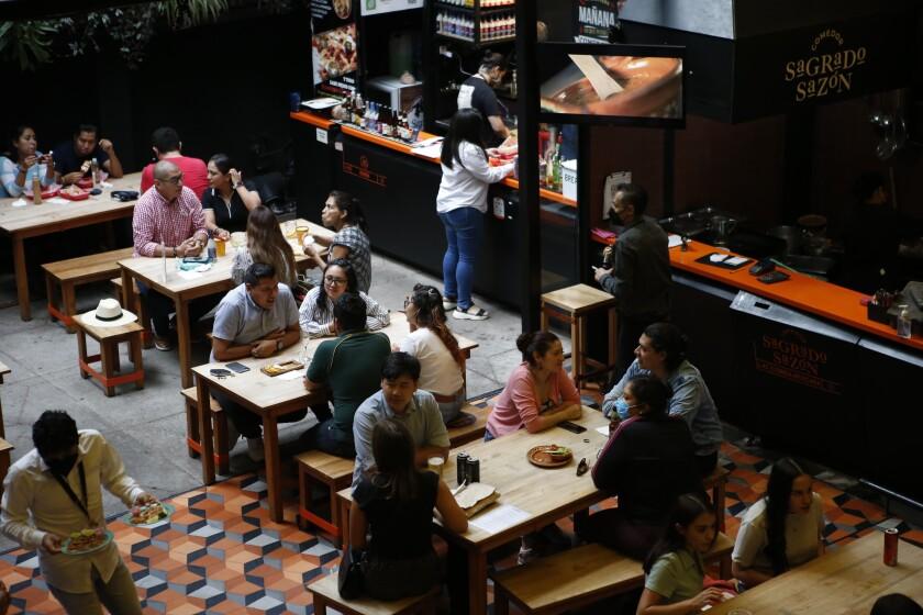 Comensales en la plaza de negocios de comida Huerto Roma, el 10 de julio de 2021, en la Ciudad de México. (AP Foto/Ginnette Riquelme)
