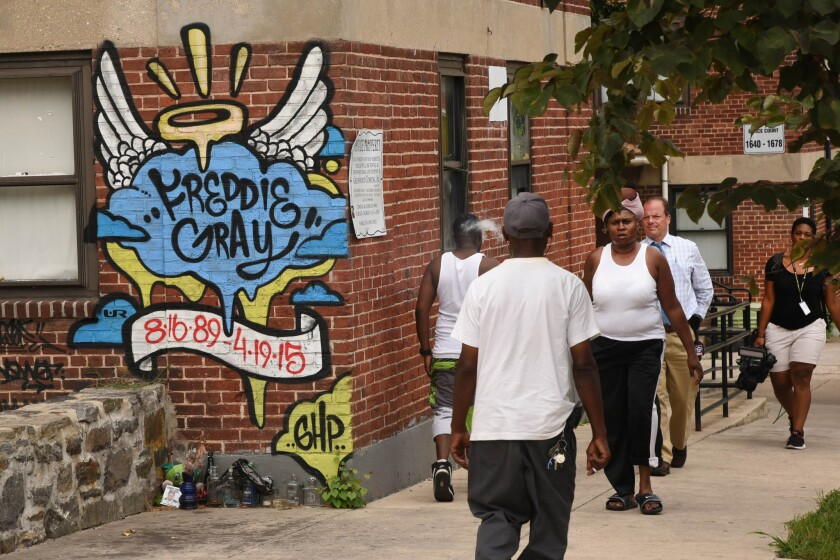 People in Baltimore walk past the site where Freddie Gray was arrested. His death in police custody helped spark a sweeping pact to revamp the department.