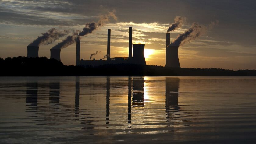 FILE - In this June, 3, 2017, file photo, the sun sets behind Georgia Power's coal-fired Plant Scher
