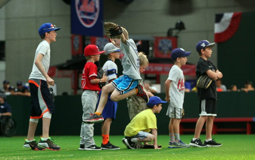 Oliver Anderson, 7, center, of Yakima Washington jumps for joy during practice fielding balls toward home plate at The Diamond during All-Star Game Fanfest.  He was visiting his grandparents who live in San Diego.