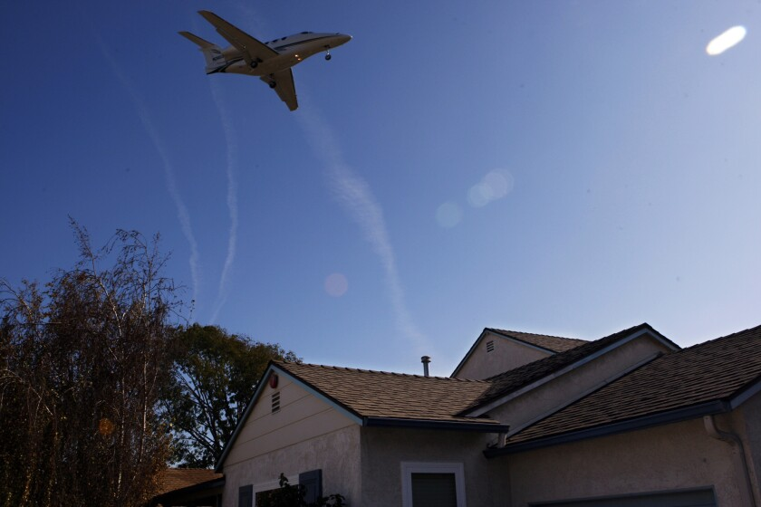 A plane flies over a Mar Vista home on approach to Santa Monica Airport. Noise and emissions from planes passing overhead has fueled an effort to close all or part of the airport.