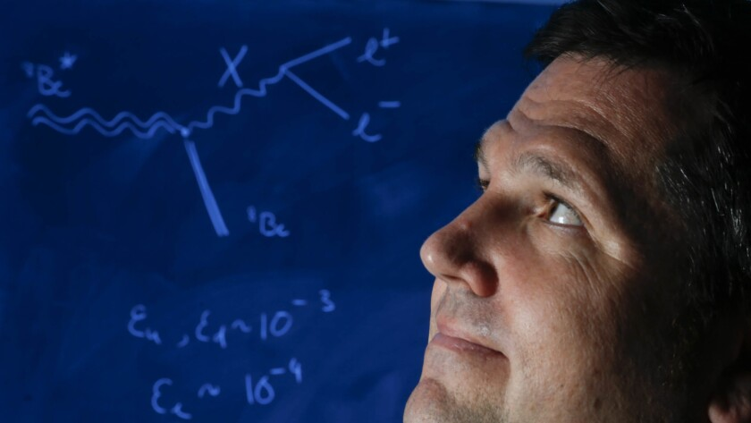 Tim Tait, Ph.d., a theoretical physicist at UC Irvine stands next to a chalkboard with calculations that show a few of the details of a study that he co-authored about a tiny, unseen force could potentially alter our basic understanding of the universe.
