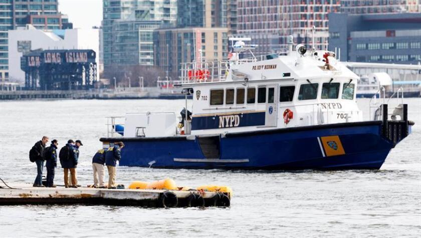 Efectivos de cuerpos de seguridad conversan en el lugar del accidente, en el estrecho del East River de Nueva York, Estados Unidos, el pasado 12 de marzo del 2018, un día después de que un helicóptero se estrellara contra el agua. EFE/Archivo