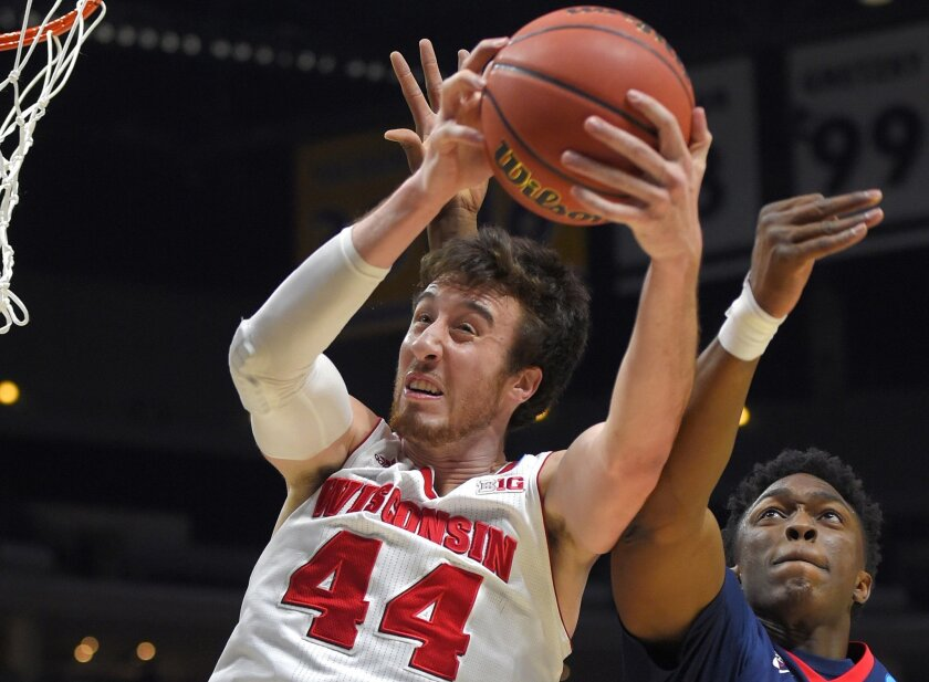 FILE - In this March 28, 2015, file photo, Wisconsin's Frank Kaminsky (44) grabs a rebound in front of Arizona's Stanley Johnson during the first half of a college basketball regional final in the NCAA Tournament in Los Angeles. Kaminsky, the 7-footer who anchored Wisconsin's run to a second straight Final Four, is the runaway choice as The Associated Press' player of the year, Friday, April 3, 2015.(AP Photo/Mark J. Terrill, File)