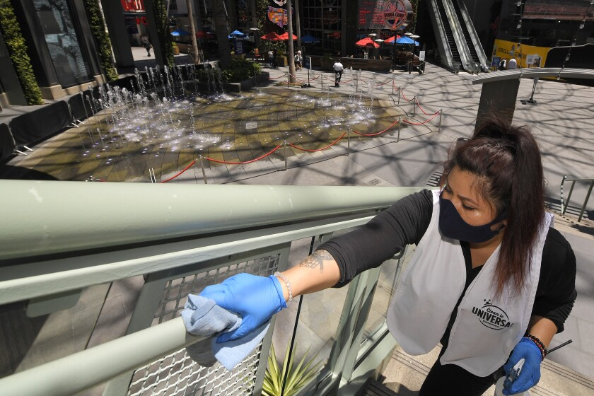 """FILE - In this Thursday, June 11, 2020 file photo, Andrea Castaneda cleans the railings at Universal CityWalk near Universal City, Calif. On Friday, June 12, 2020, the Centers for Disease Control and Prevention posted guidelines to reduce the risk of COVID-19 coronavirus infection, along with a set of """"considerations"""" for organizing and attending mass gatherings, as people emerge from stay-at-home lock downs and attempting some semblance of normal life. (AP Photo/Mark J. Terrill)"""