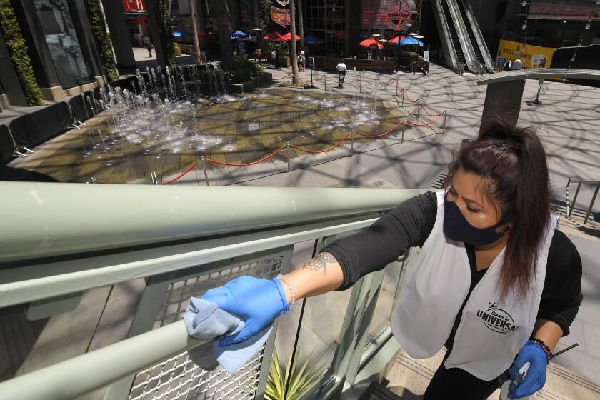 Andrea Castaneda cleans railings June 11 at Universal CityWalk near Universal City.