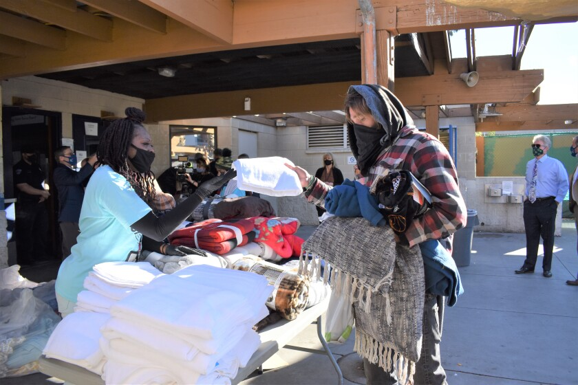 Neil Good Day Center Supervisor Antionette Miles (left) hands a towel to a homeless person at the center Tuesday.