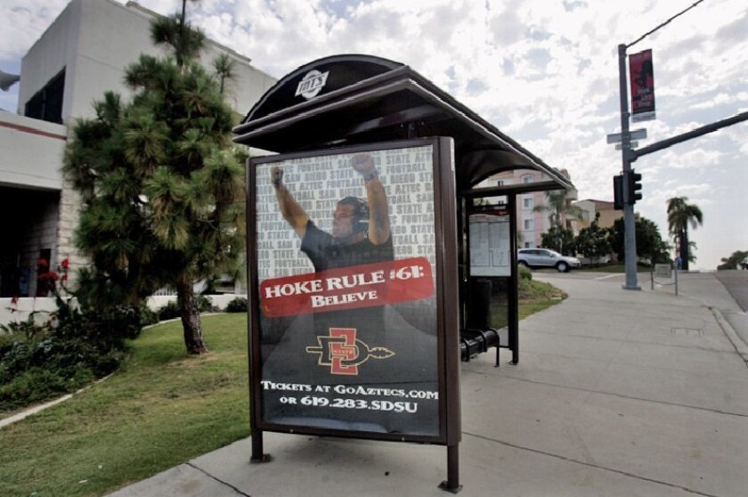 The marketing of Aztecs coach Brady Hoke has begun, including his picture at a bus stop near campus. (Laura Embry / Union-Tribune)