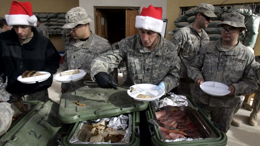 U.S. Army soldiers queue for their Christmas lunch at K–wal combat outpost in the village of Shakarat, Iraq on Dec. 25, 2007.