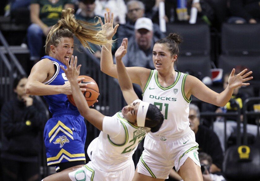 South Dakota State's Lindsey Theuninck, left, is called for a player control foul under pressure from Oregon's Minyon Moore, center, and Erin Boley during the first quarter of an NCAA college basketball game in Eugene, Ore., Sunday, Dec. 8, 2019. (AP Photo/Chris Pietsch)