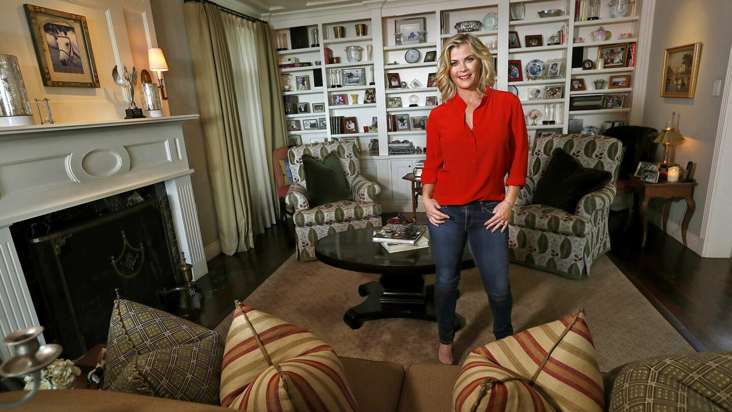 """""""I love all the wood in it and the bookshelves,"""" the actress says of her living room, which is a family gathering place."""