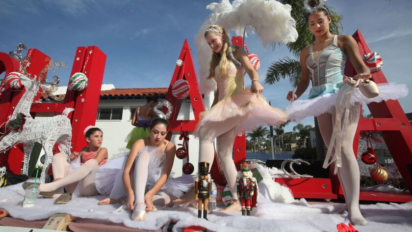 Ballerinas from the Ooh La La Dance Academy climb aboard the float for a new restaurant, Le Petit Chateau, prior to the start of the La Jolla Christmas Parade in this 2014 file photo.
